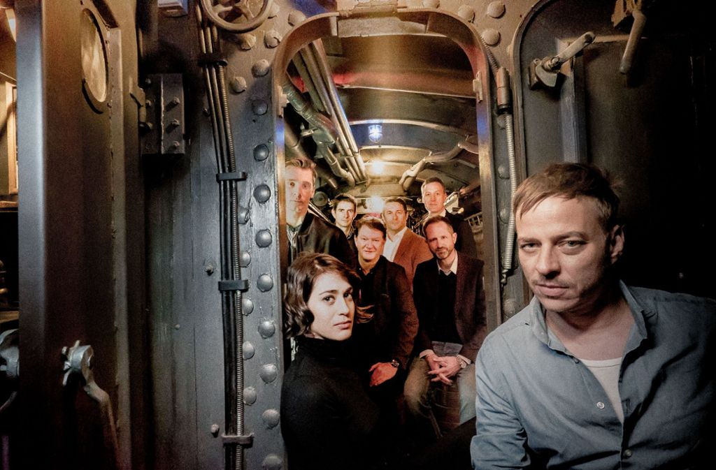 """""""Game of Thrones"""" trifft auf """"Masters of Sex"""": Tom Wlaschiha (vorn) und Lizzy Caplan gehören zu den Stars in dem Serien-Sequel von """"Das Boot"""". Hinter den beiden drängeln sich beim Gruppenfoto im U-Boot die Macher der TV-Fortsetzung des Filmklassikers. Foto: Bavaria Fiction GmbH"""