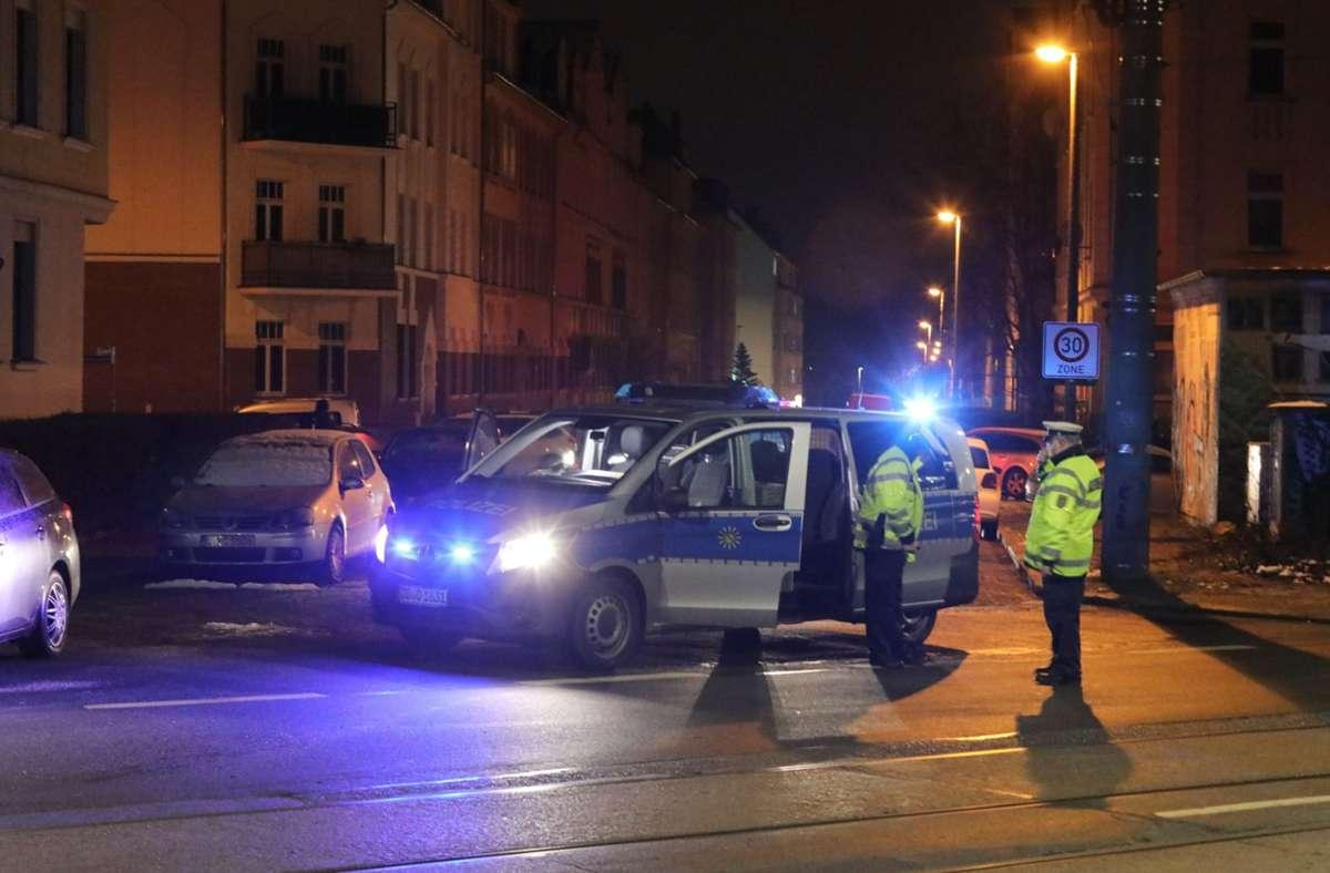 Polizisten stehen an einer durch ein Polizeifahrzeug blockierten Straße. Das Landeskriminalamt Sachsen hat am Mittwochmorgen eine groß angelegte Razzia in Dresden und Leipzig gestartet Foto: dpa