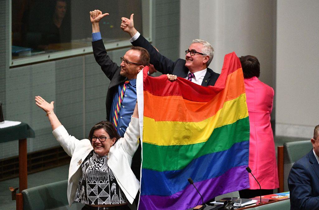 Parlamentsmitglied Cathy McGowan, Adam Brandt und Andrew Wilkie jubeln nach dem Parlamentsbeschluss in Canberra. Foto: dpa