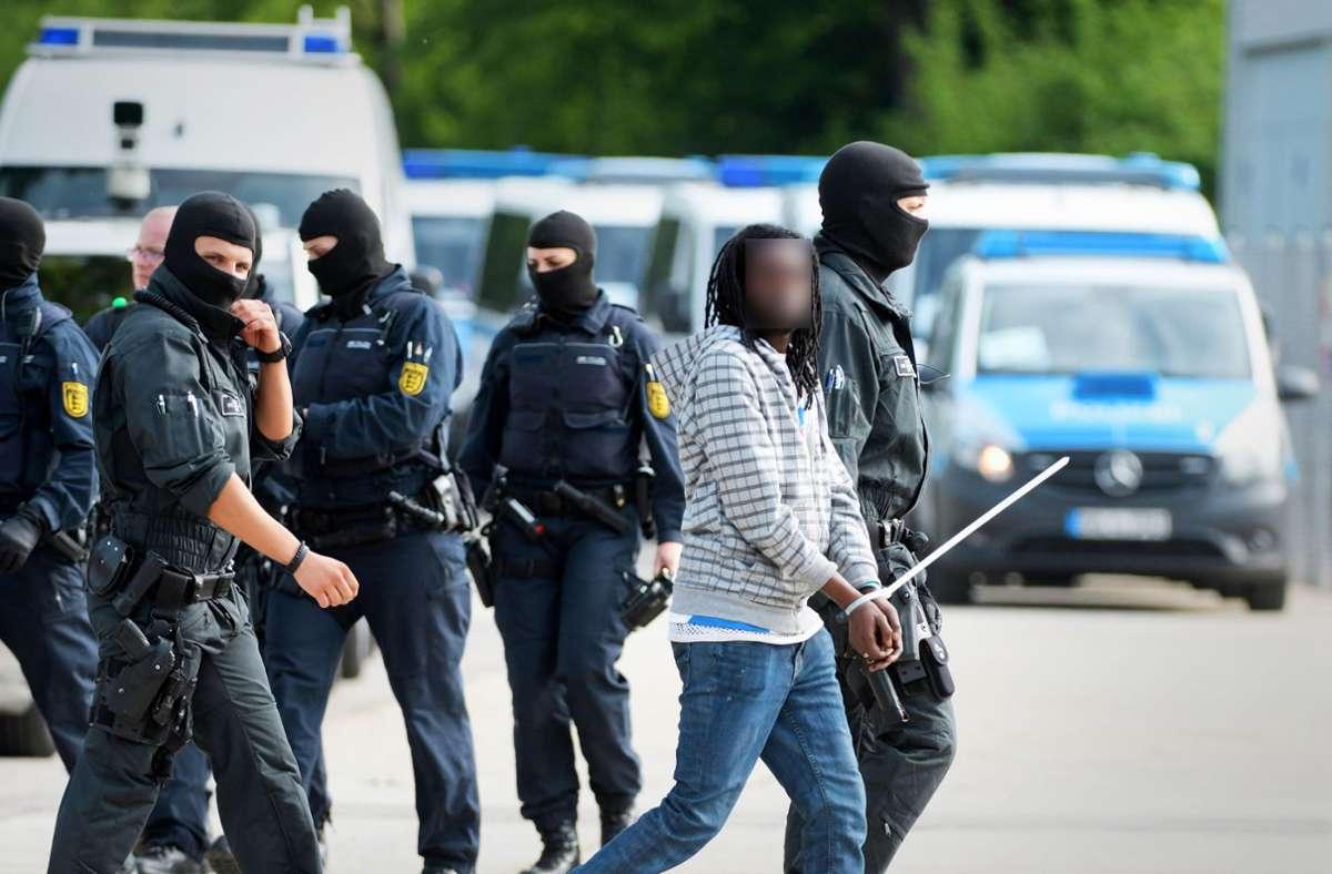 Ein Flüchtling wird wie ein Schwerverbrecher abgeführt: Bei ihrer Großrazzia in der Lea in Ellwangen ist die Polizei nach Ansicht des Stuttgarter Verwaltungsgerichts zu weit gegangen. Foto: dpa/Stefan Puchner