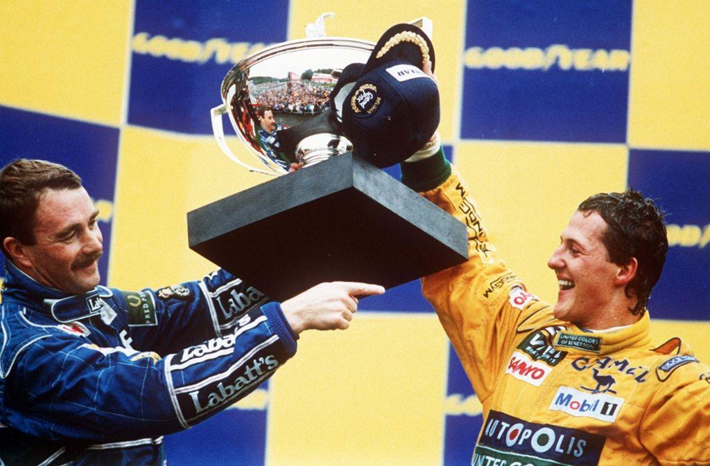 """Michael Schumacher gewinnt 1992 in Spa sein erstes Formel-1-Rennen und feiert mit dem zweitplatzierten Briten Nigel Mansell (links). Seit diesem Erfolg bezeichnete Schumi die Strecke in den belgischen Ardennen als sein """"Wohnzimmer"""". Foto: dpa"""
