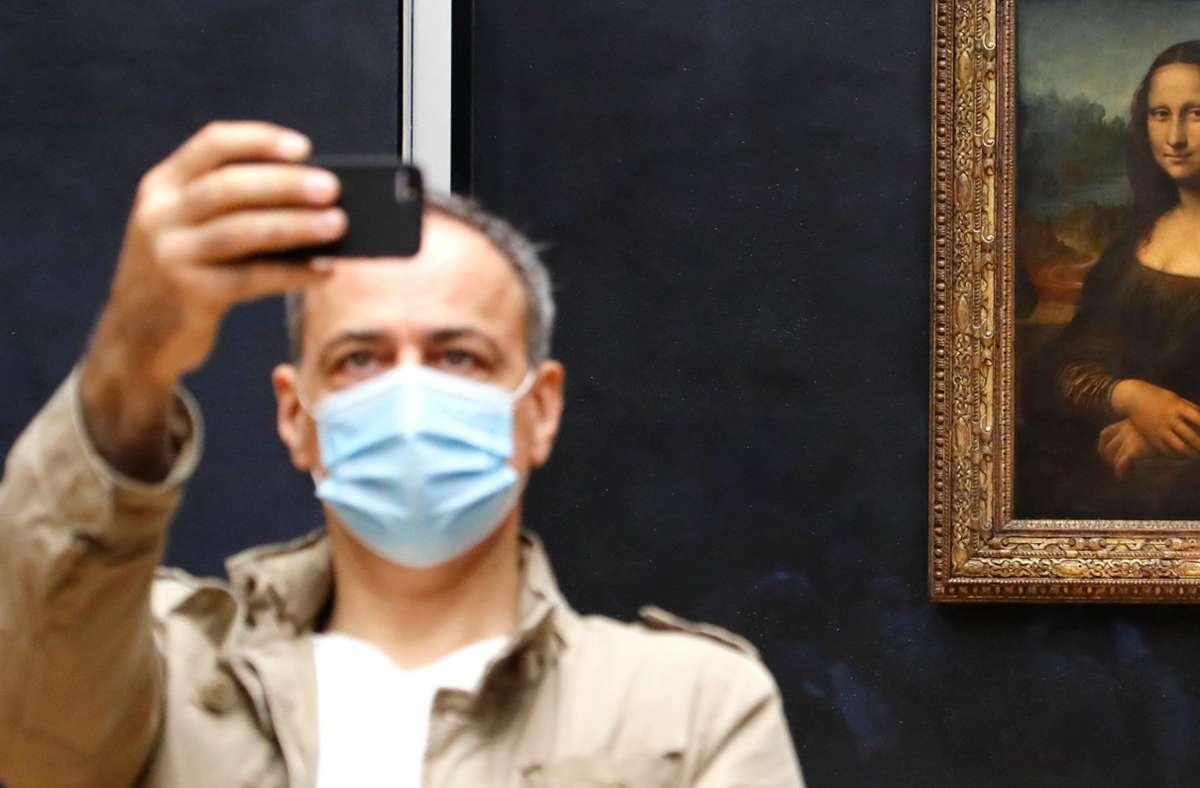 Die Mona Lisa im Louvre ist nur mit Maske zu bestaunen. Auch in Frankreich gehört sie zum Alltag, wirklichen Streit um die Maskenpflicht gibt es nicht. Foto: AFP/Francois Guillot
