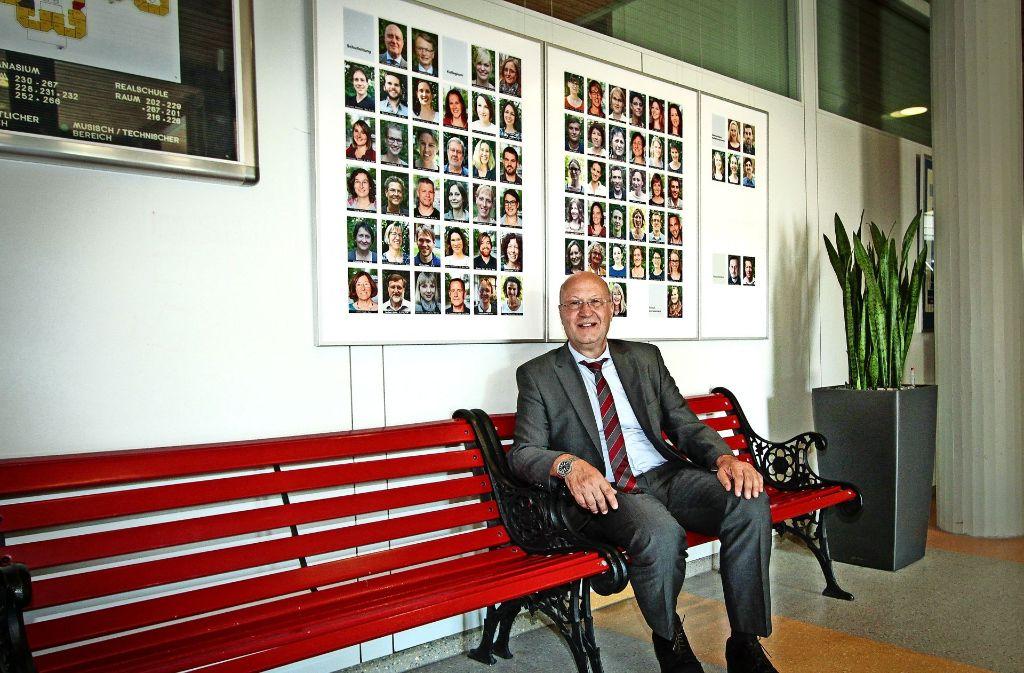 Die rote Bank hat Kultstatus in der Schule. Sie steht im Eingangsbereich,  unter den Fotos des Lehrerkollegiums. Statt Wolfgang Zakrzewski sitzen dort meist Schüler. Foto: factum/Bach