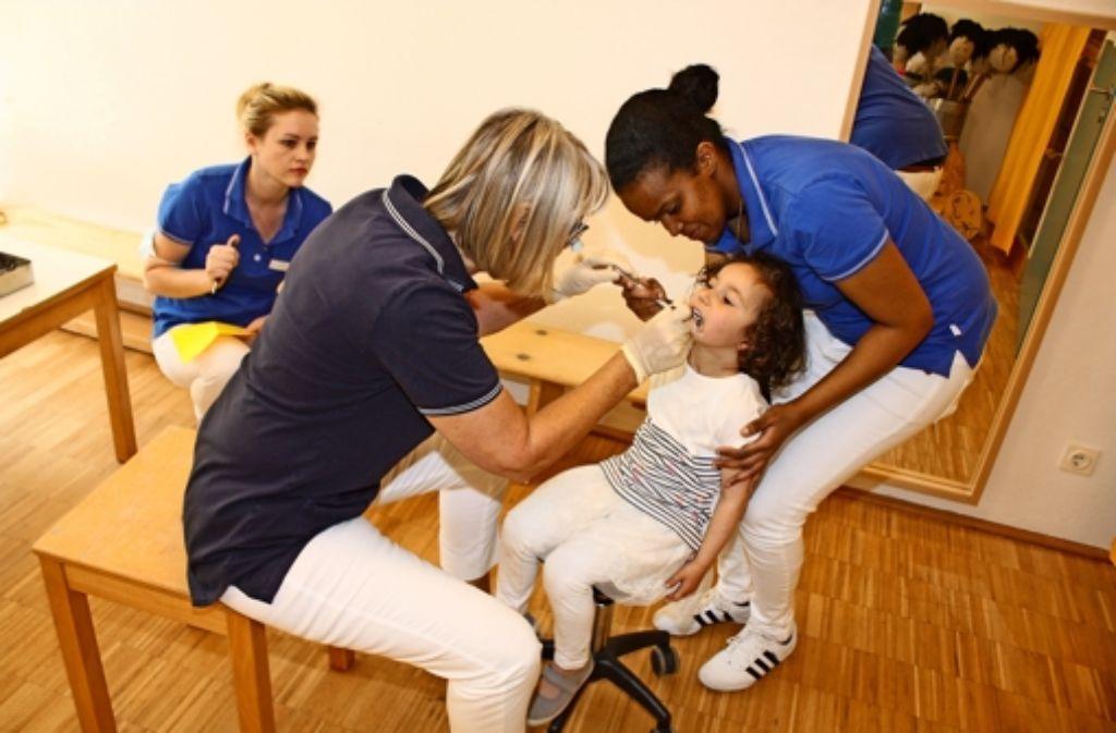 Die Zahnärztin Angelika Krämer untersucht  Alina, unterstützt von ihren Helferinnen Lilli Krüger  und Hibo Barre (von links). Foto: Stahlberg