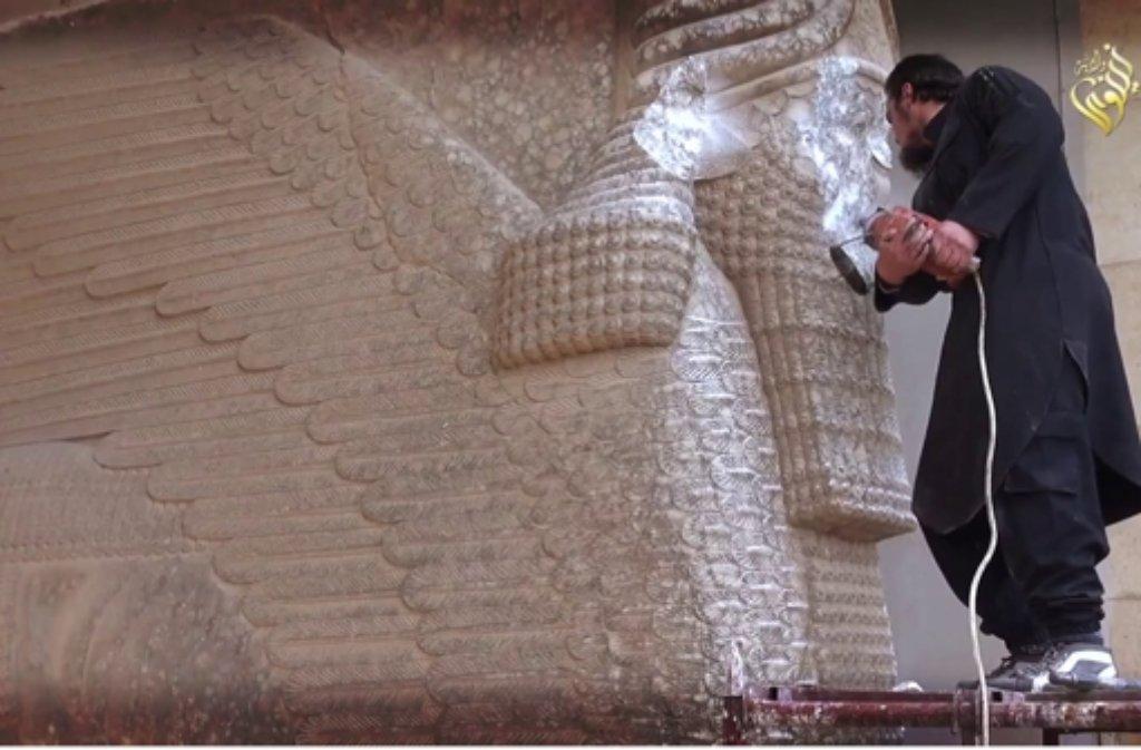 Mit einem Presslufthammer zerstört ein Mitglied der Terrormiliz Islamischer Staat eine Türhüterfigur in Ninive. Das Foto ist ein Screenshot aus einem Video, das von IS veröffentlicht wurde.  Foto: Islamischer Staat/Internet/dpa