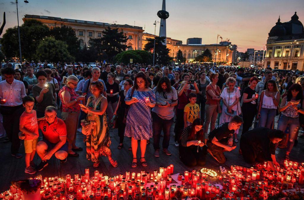 Zahlreiche Menschen zünden im Gedenken an Alexandra vor dem rumänischen Innenministerium Kerzen für die ermordete 15-Jährige an. Foto: AFP
