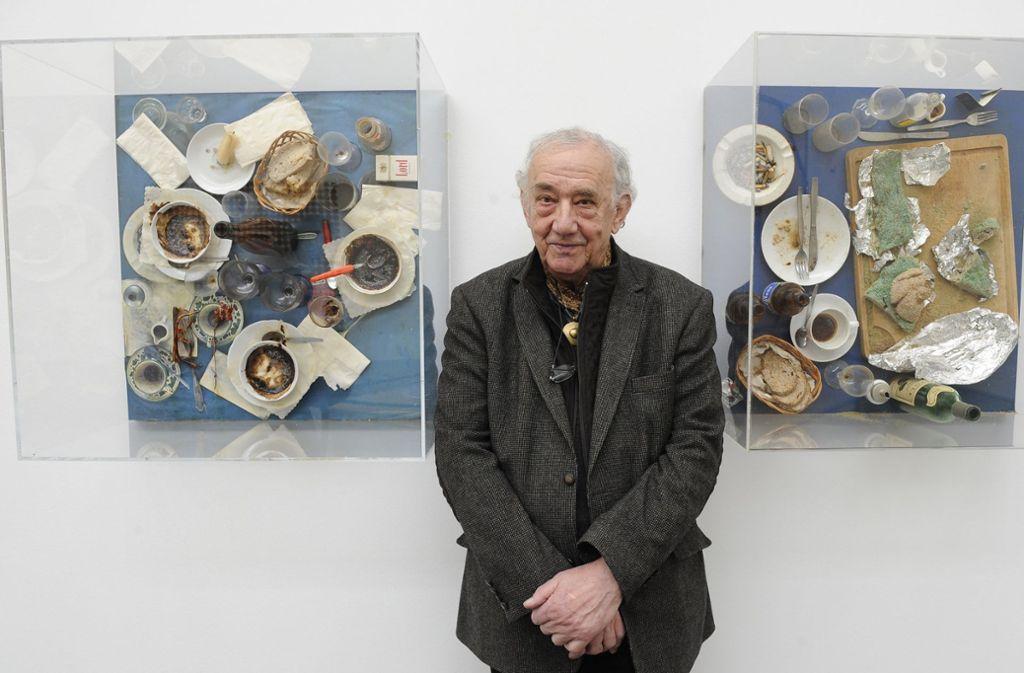"""Der Künstler Daniel Spoerri steht 2009 in Düsseldorf vor den Kunstwerken """"Tableau piege"""". Foto: dpa/Achim Scheidemann"""