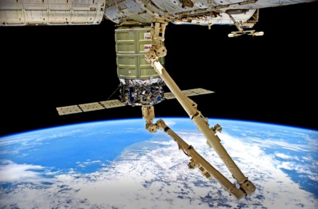 Der Roboterarm der Internationalen Raumstation dockt im Juli 2014 den Frachter Cygnus von Orbital Sciences an. Foto: Nasa