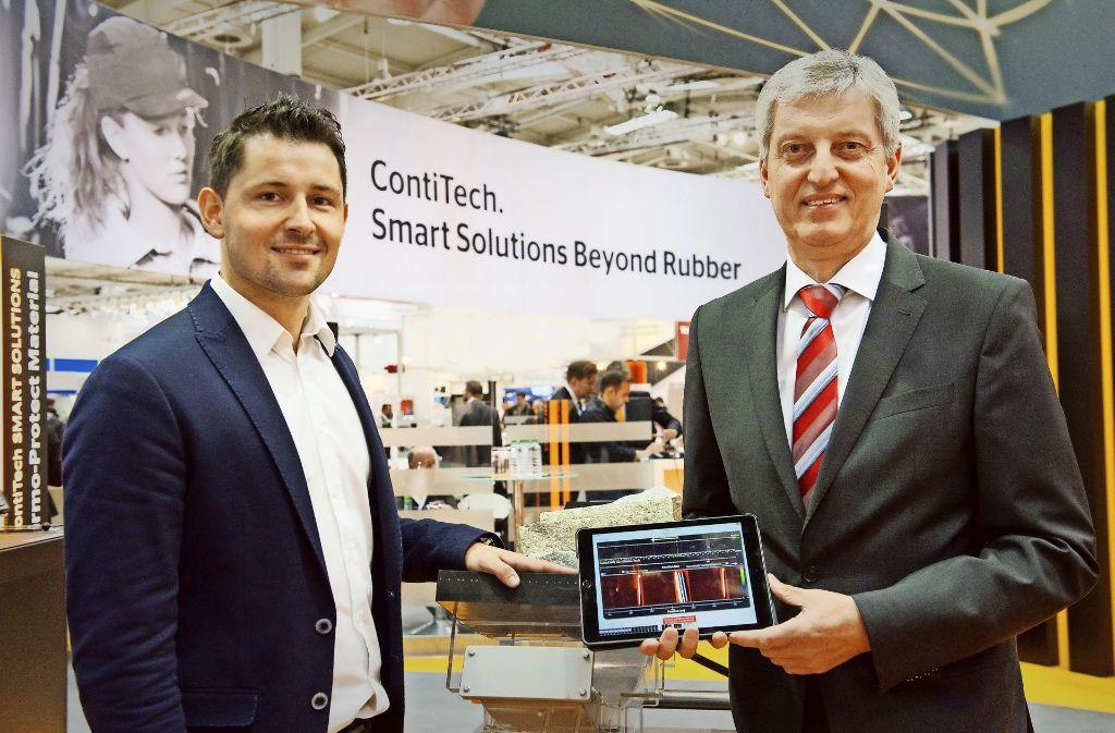 Conti-Vorstandsmitglied  Hans-Jürgen Duensing (rechts) und Anwendungstechniker Patrick Raffler halten auf der Hannover Messe das Tablet  hoch, auf dem die Ergebnisse der Messungen eines sensorgesteuerten Förderbands angezeigt werden. Foto: Conti
