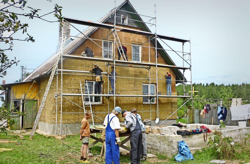 Freiwillige dämmen  die einfachen Dorfhäuser aus Holz und Lehm mit Schilfmatten. Foto: Christof Schill