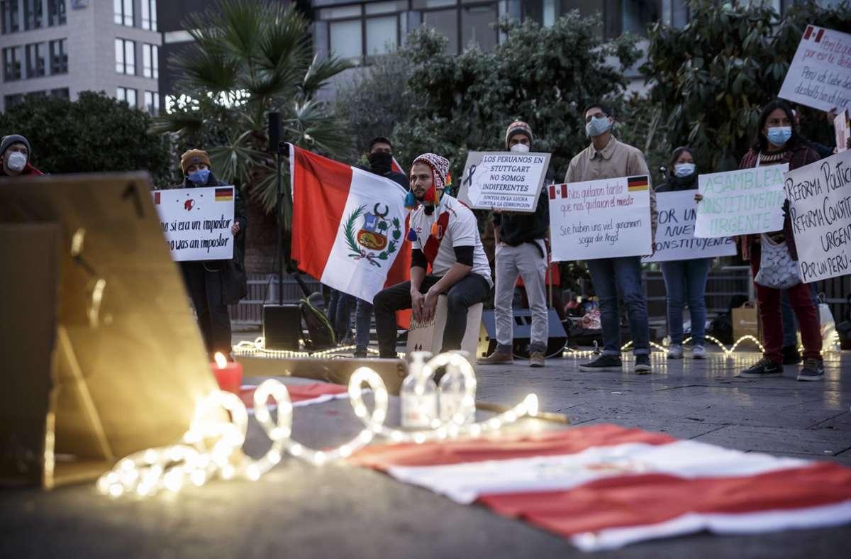 Rote und weiße Kerzen brennen auf dem Sockel der Spiegelskulptur vor den Portraits der beiden Männer, die vor einer Woche bei Demonstrationen in Peru durch Polizeigewalt starben. Foto: Lichtgut/Julian Rettig