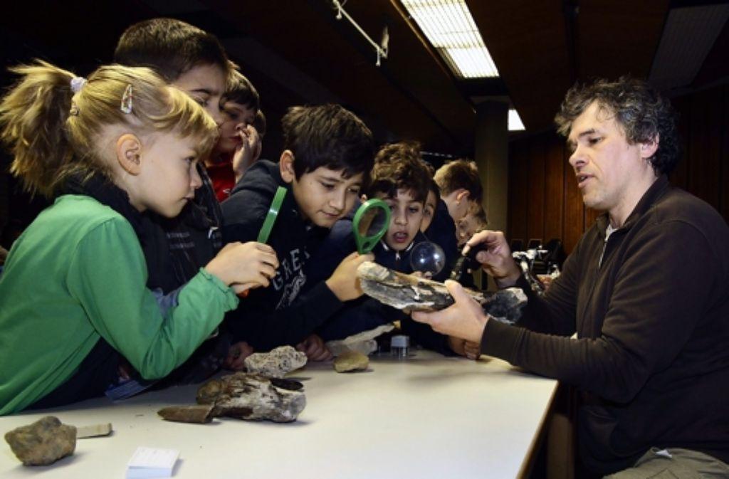 Der Geologe Ralf Laternser zeigt den Kindern einen Dinosaurierknochen. Foto: factum/Bach
