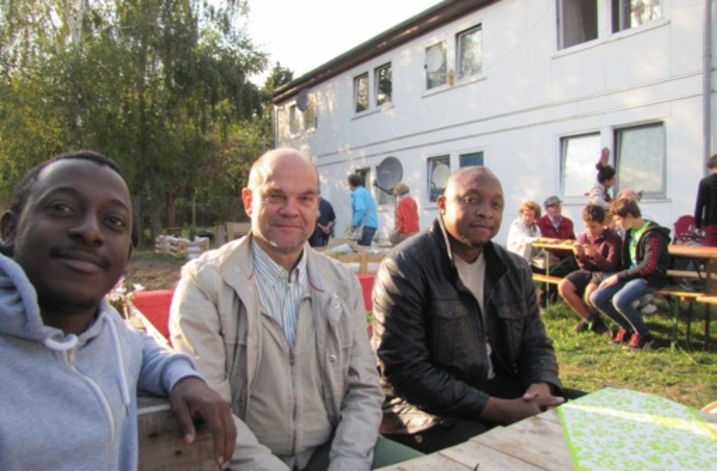 Der Nachbar Karsten Hoffmann (Mitte) unterhält sich mit den Flüchtlingen Silas Dingoke (l.) und Marko Kengne (r.) aus Kamerun über deren Zukunft in Deutschland. Foto: Julia Schuster