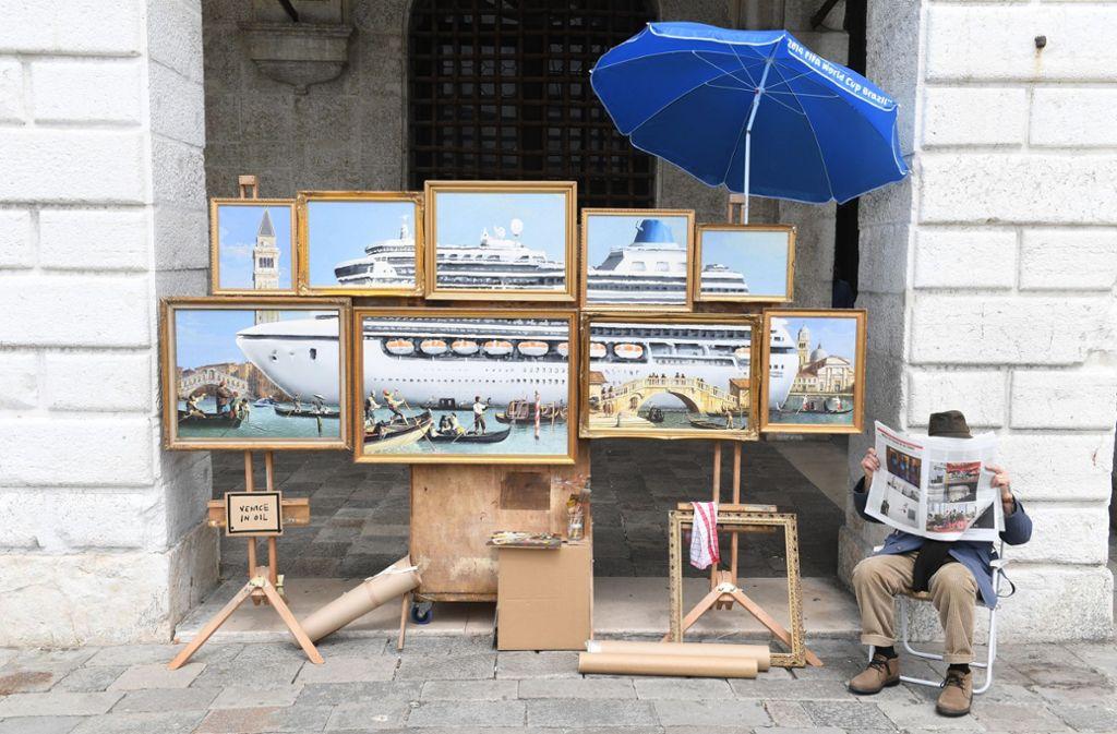 Kunstbiennale 2019: Ein Straßenmaler bietet in der Nähe des Markusplatzes Kunstwerke zum Verkauf an. Foto: dpa/Felix Hörhager