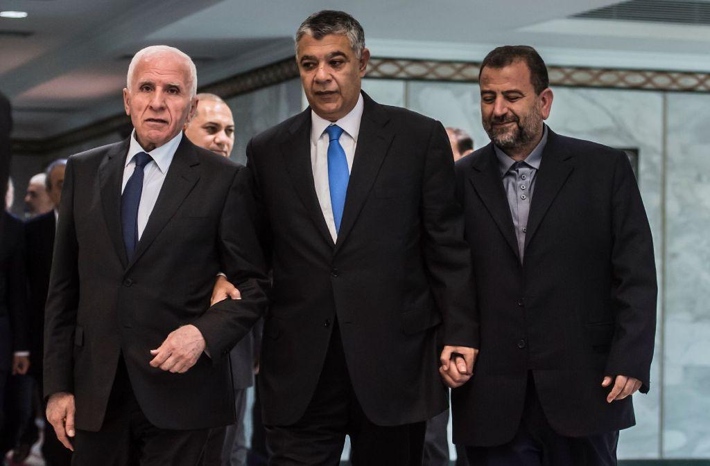Durch Khaled Fawzi, Chef des ägyptischen Geheimdienstes, als Vermittler reichen sich die Fatah, vertreten durch Azzam al-Ahmad (links) und Hamas, durch Saleh al-Aruri (rechts), die Hand. Foto: AFP