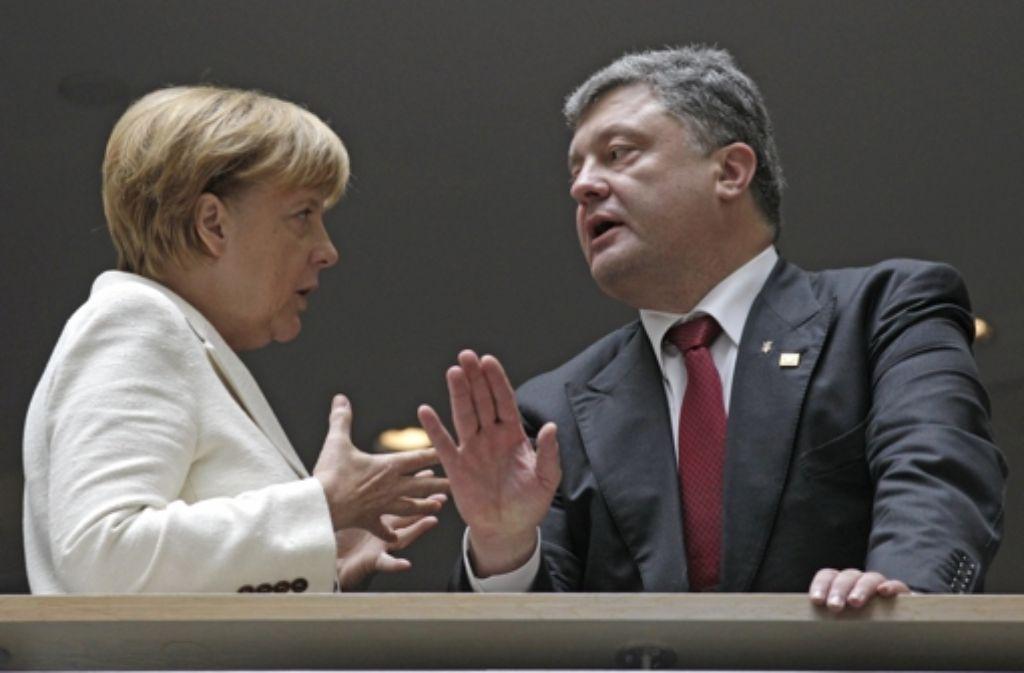 Ernste Mienen beim Gespräch der Kanzlerin mit dem ukrainischen Präsidenten Poroschenko Foto: AP