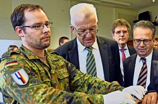 Ministerpräsident Winfried Kretschmann (Mitte) und der Präsident des Bundesamtes für Migration und Flüchtlinge (BAMF), Frank-Jürgen Weise (rechts), beobachten im Patrick-Henry-Village die Abnahme der Fingerabdrücke bei einem Flüchtling. Foto: dpa