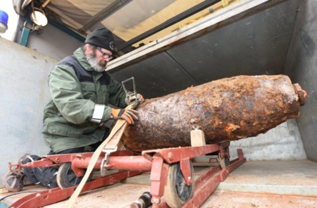 Ein Mitarbeiter des Kampfmittelräumdienstes befestigt die 500-Kilogramm-Fliegerbombe in Freiburg für den Abtransport. Foto: dpa