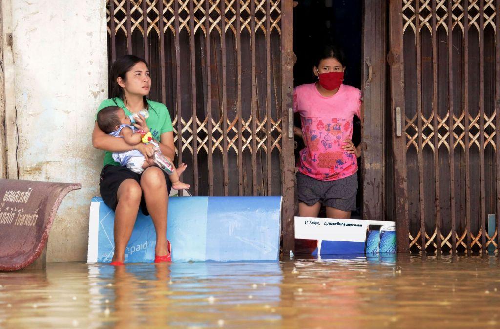 Sie harren der Dinge – Bewohner eines überfluteten Hauses in dem Dorf Chauat im Süden Thailands. Foto: AFP