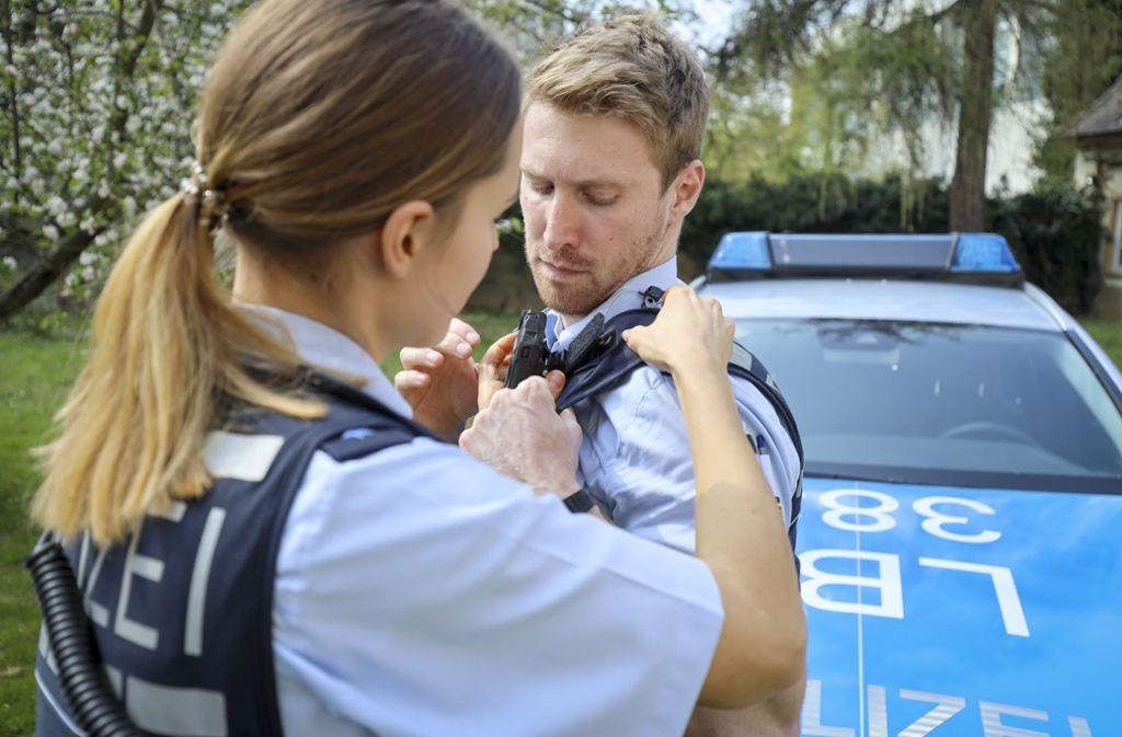 Die Streifenpolizistin Laura Geißler hilft ihrem Kollegen Nils Mayer, die kleine Kamera an der Schulter anzubringen. Foto: factum/Simon Granville