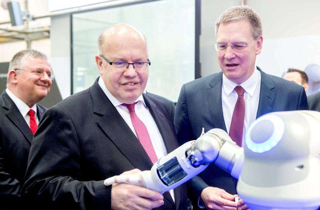 Festo-Chef  Oliver Jung (rechts) mit Wirtschaftsminister Peter Altmaier. Die    Roboterhand  von Festo ist ein  Publikumsmagnet  auf der Messe in Hannover. Foto: dpa