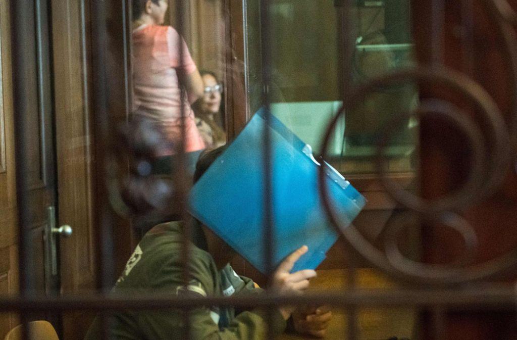 Der Angeklagte versteckt im Gerichtssaal sein Gesicht hinter einem Ordner. Foto: AFP