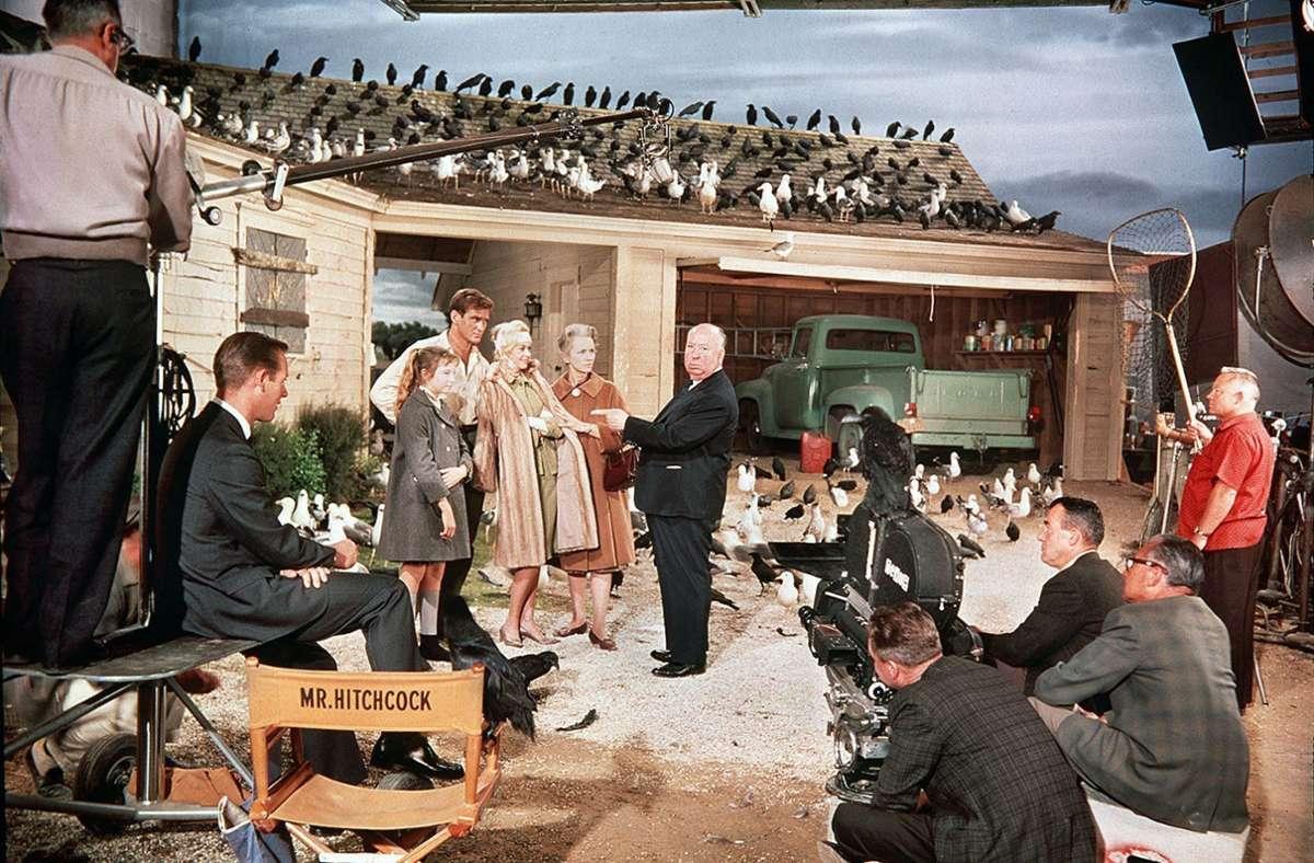 """Daphne du Mauriers Kurzgeschichte """"Die Vögel"""" war inspiriert von Arthur Machens Erzählung """"Der Schrecken"""" von 1917. Hier eine Szene von den Dreharbeiten zum Film (1963) mit dem berühmten Thriller-Regisseur Alfred Hitchcock (Mitte). Foto: picture-alliance / dpa/WDR/ARD"""