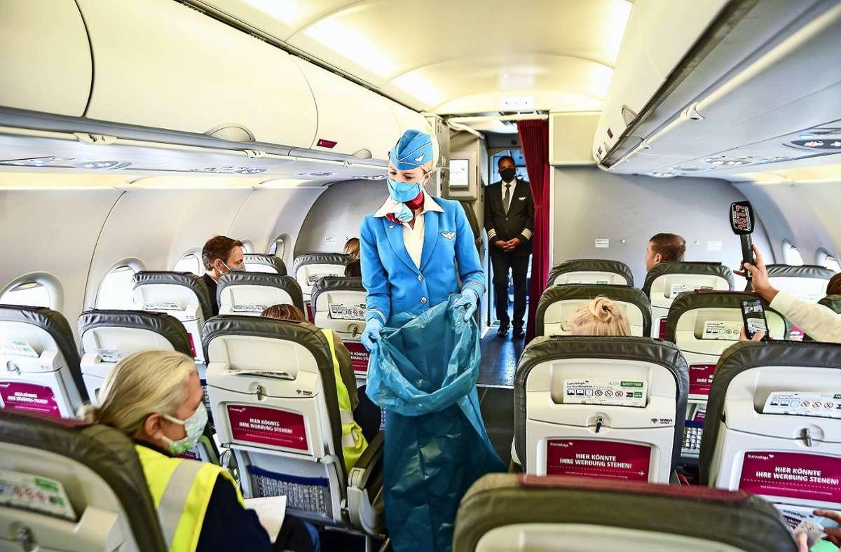 Flugbegleiterin in neuer Mission: Die Tücher zur Händedesinfektion werden später wieder eingesammelt Foto: Lichtgut/Ferdinando Iannone