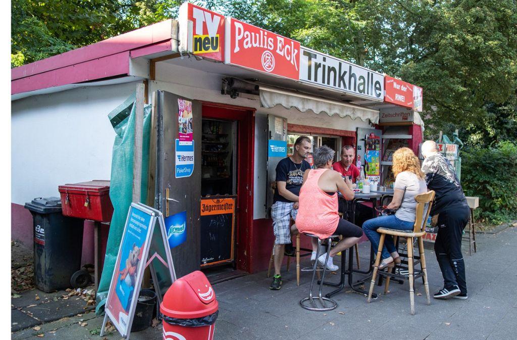 """Kiosk-Besitzer Thomas Paul (links) sitzt mit Kunden vor seiner Trinkhalle """"Paulis Eck"""" in Essener Stadtteil, Altenessen. Foto: dpa"""