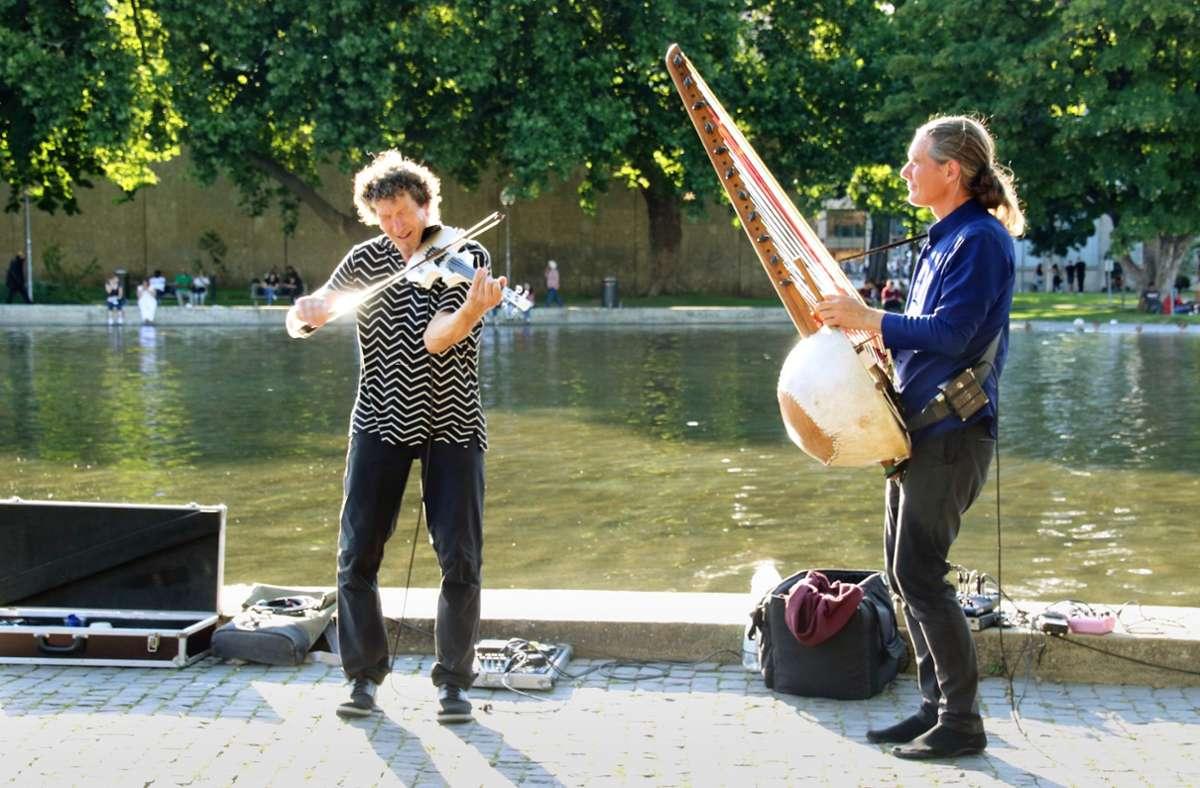 Stefan Charisius an der  westafrikanischen Harfe (rechts) und Martin Schnabel an der Geige spielen  am Eckensee. Die Wasserkonzerte sollen  mit Unterstützung des Landes bis zum 20. September gehen. Foto: M Trommsdorff