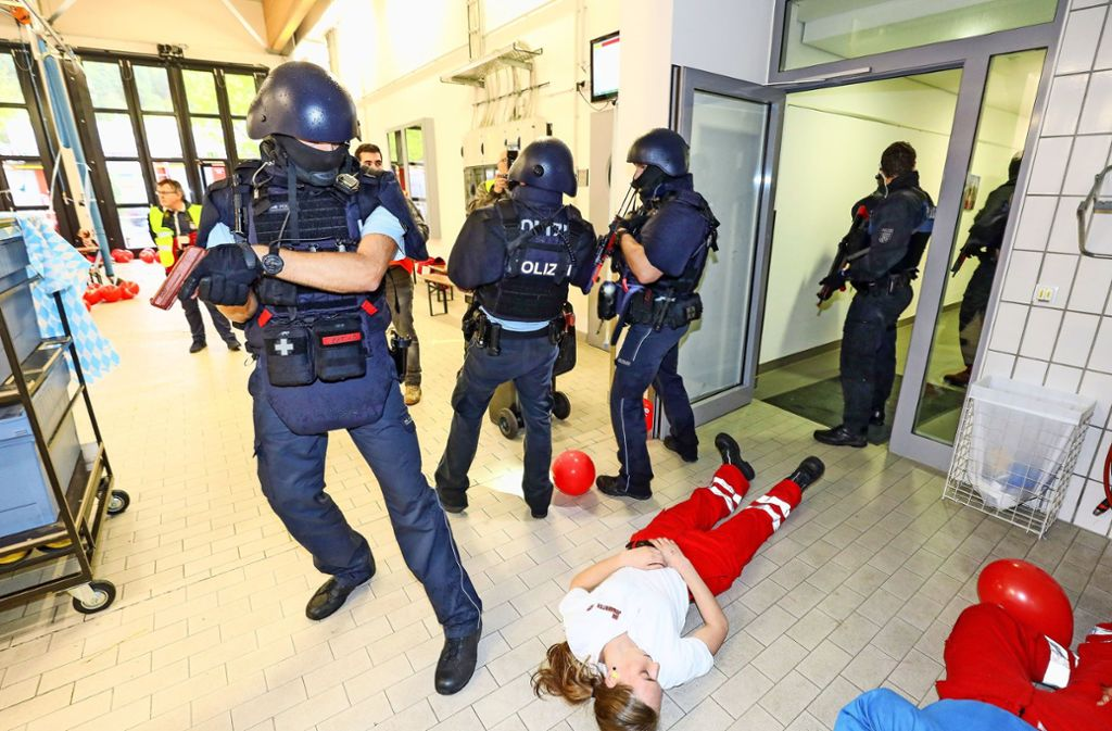 Wie im Sonntagskrimi: Polizeibeamte sichern das Gebäude. Die Maschinenpistolen sind aber Attrappen. Foto: