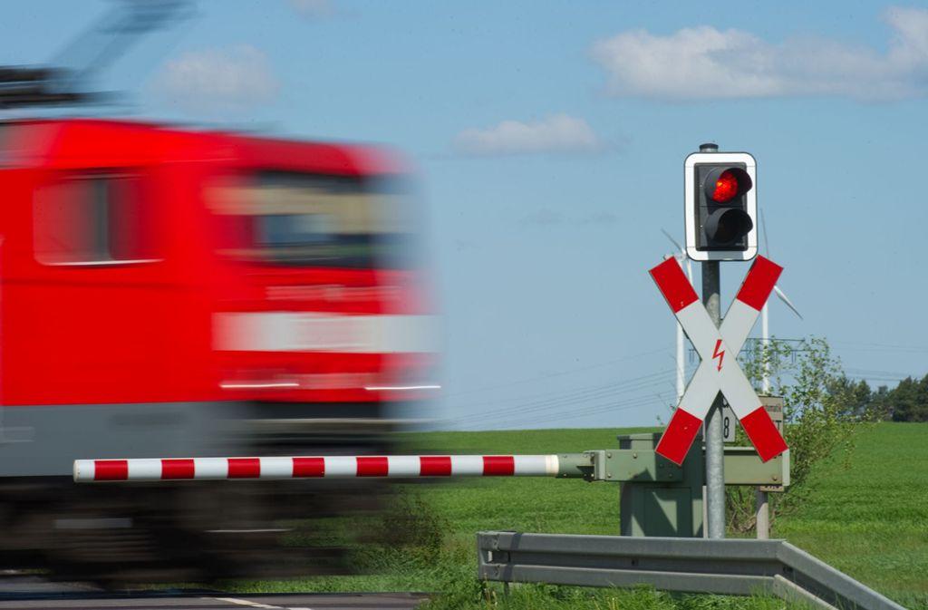 Halt! Ein Zug fährt bei  Jacobsdorf in Brandenburg an einem geschlossenem Bahnübergang mit Andreaskreuz und rotem Lichtsignal  vorbei. Foto: dpa/Patrick Pleul