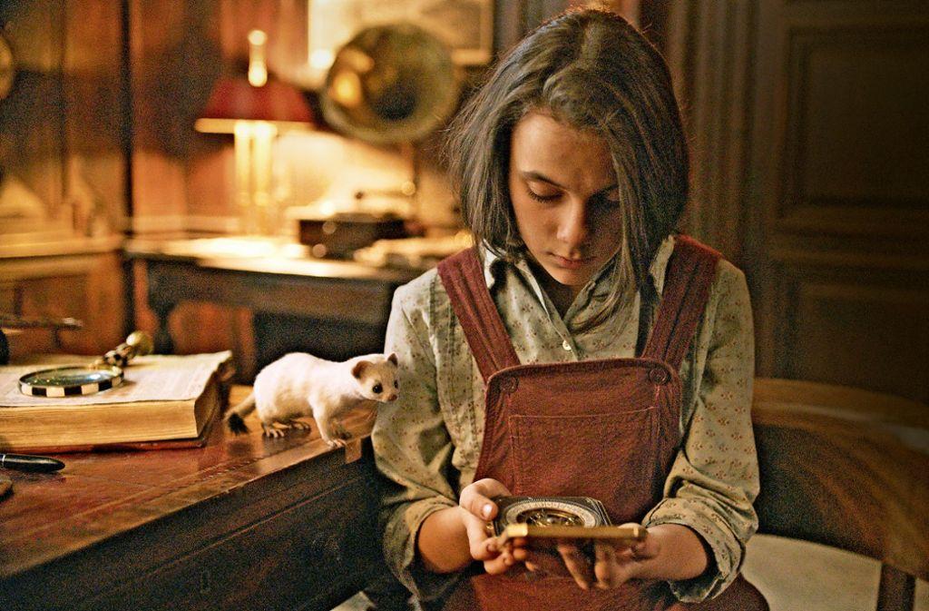 Lyra (Dafne Keen) begutachtet zusammen mit ihrem Dæmon Pantalaimon den Goldenen Kompass, den ihr der Rektor des Jordan College in Oxford geschenkt hat. Foto: HBO/Sky