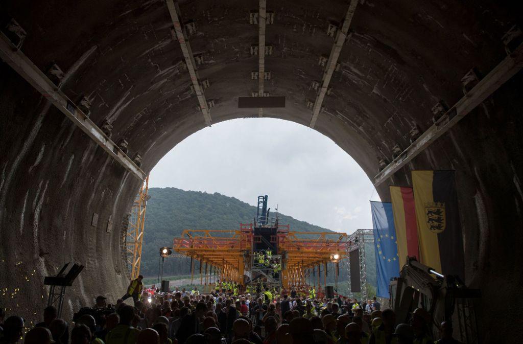 Tunnelarbeiter und Besucher der Durchschlagsfeier stehen nach dem Durchschlag im Boßlertunnel, im Hintergrund ist ein Gerüst der sich im Bau befindlichen Filstalbrücke zu sehen. Foto: dpa