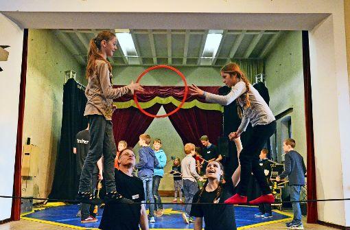 Das Gleichgewicht auf dem dünnen Seil zu halten und sich dabei noch einen Ring zuzuwerfen, ist gar nicht so leicht. Doch mit ein bisschen Hilfestellung der Trainer klappt es. Foto: Sandra Hintermayr