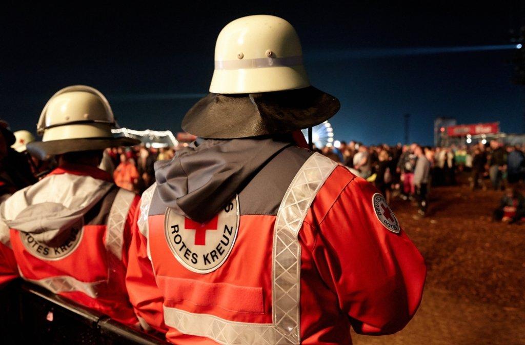 """Helfer des Deutschen Roten Kreuz (DRK) stehen beim Festival """"Rock am Ring"""" neben der Bühne"""". Bei einem Blitzeinschlag wurden zahlreiche Menschen verletzt. Foto: dpa"""