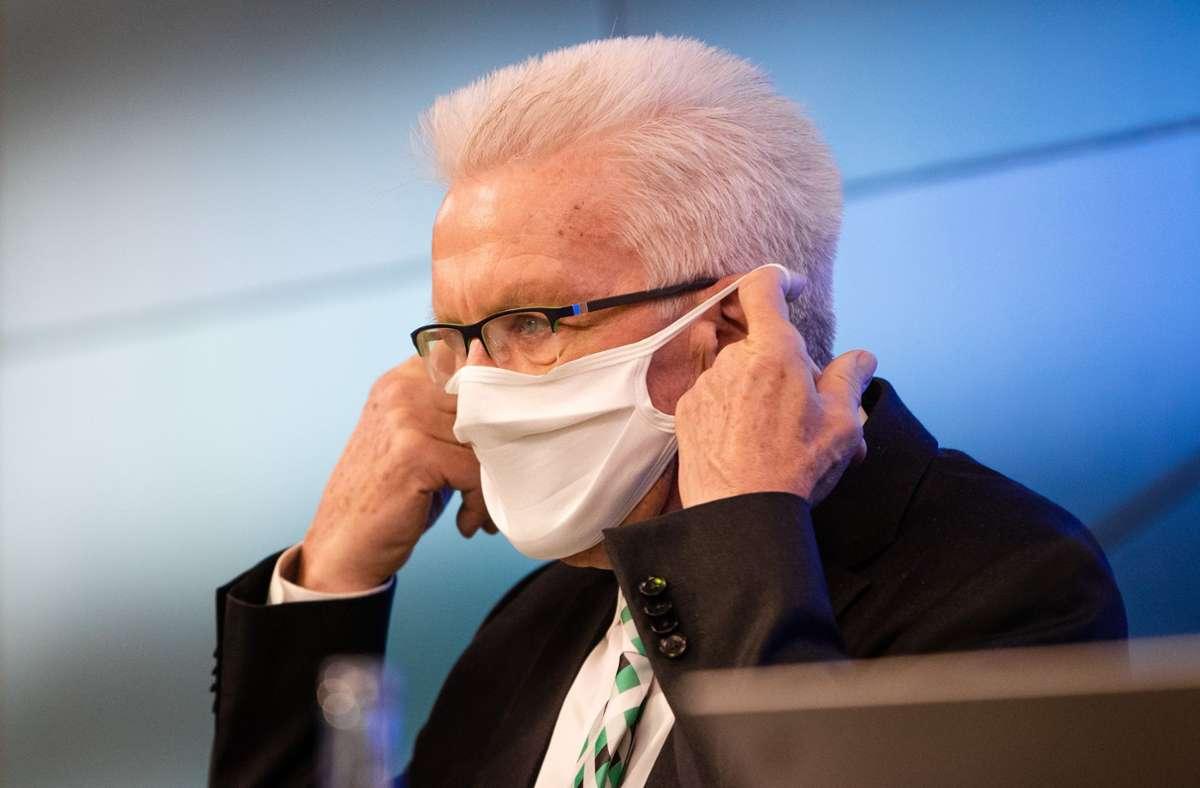 Winfried Kretschmann nimmt zu Beginn der Regierungspressekonferenz seine Nase-Mund-Schutzmaske ab. Foto: picture alliance/dpa/Christoph Schmidt