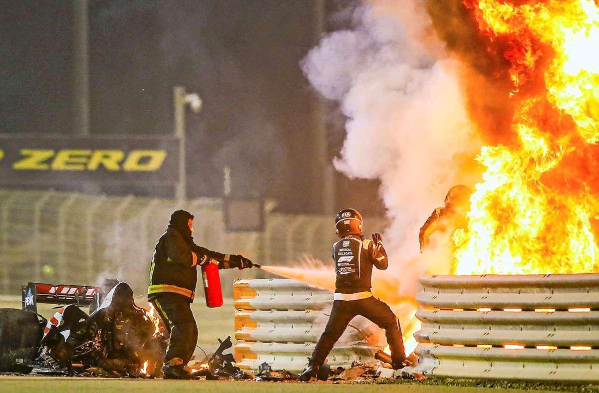 Romain Grosjean (re.) entkommt der Flammenhölle – die Rettungskräfte unterstützen ihn. Foto: imago/Andy Hone