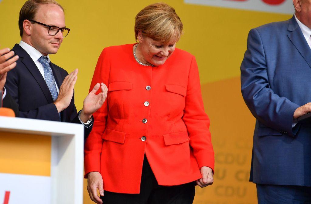 Bundeskanzlerin Merkel reagiert gelassen auf einen Fleck auf ihrer Jacke, nachdem sie mit einer Tomate beworfen worden war. Foto: dpa