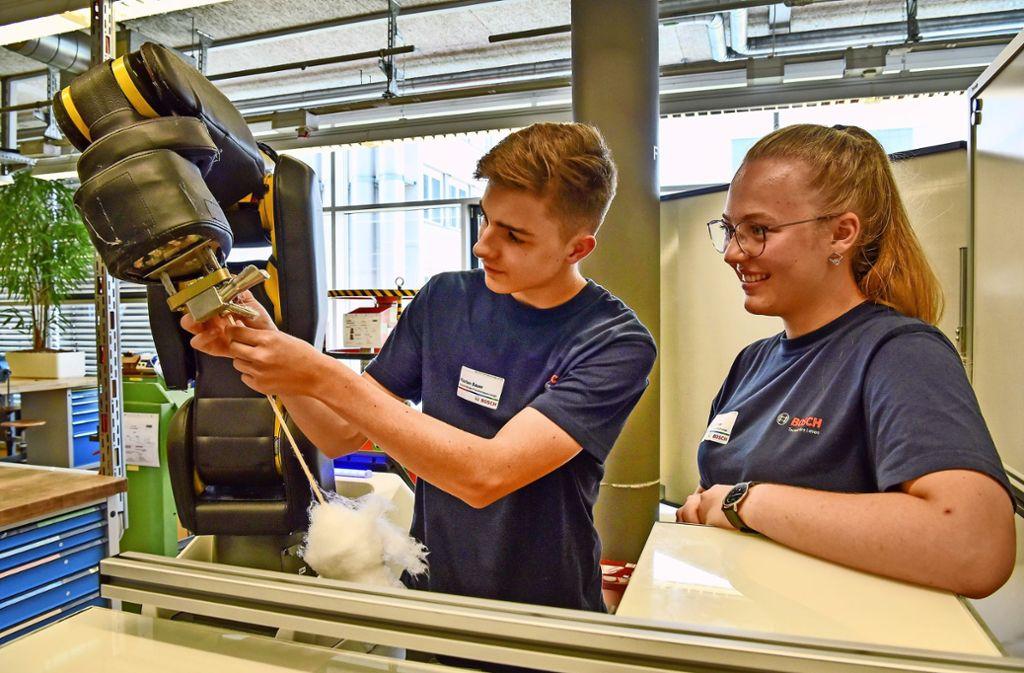 Florian Bauer und Anna Marschner, im ersten Lehrjahr als Produktionstechniker, stellen einen Roboter vor, der Zuckerwatte produziert. Foto: Tom Bloch