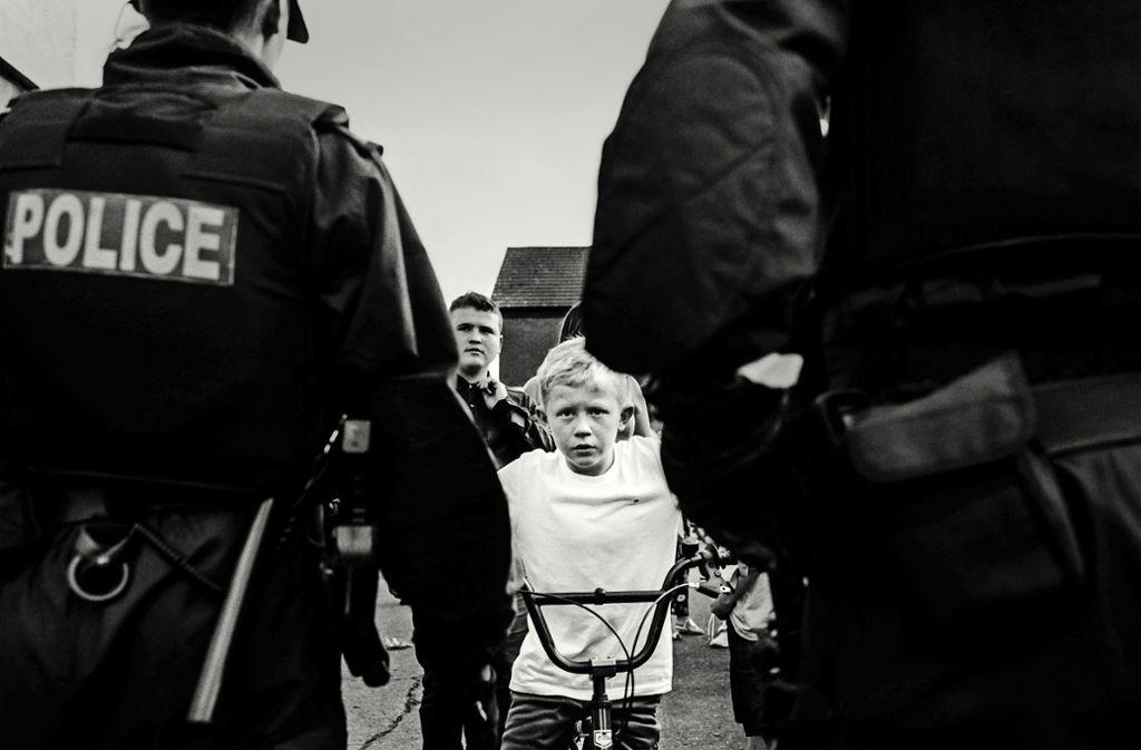 Düstere Zukunft? Der Junge Brendan blickt von seinem Fahrrad aus auf Polizisten in der Trinity Street Foto: Toby Binder