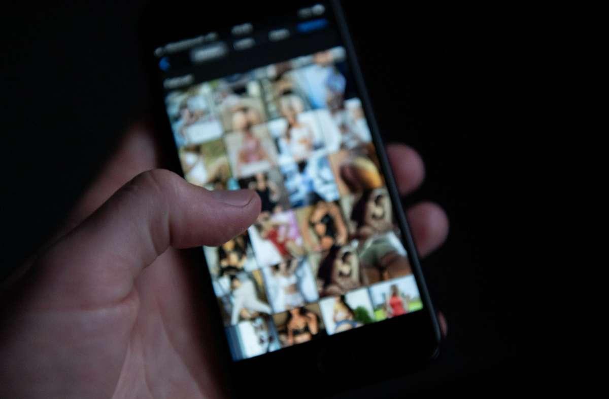 Mann schaut sich auf einem Smartphone pornografische Bilder an. In Schüler-Chatgruppen und unter Jugendlichen wird immer häufiger kinder- und jugendpornografisches Material geteilt (Symbolfoto). Foto: Silas Stein/dpa