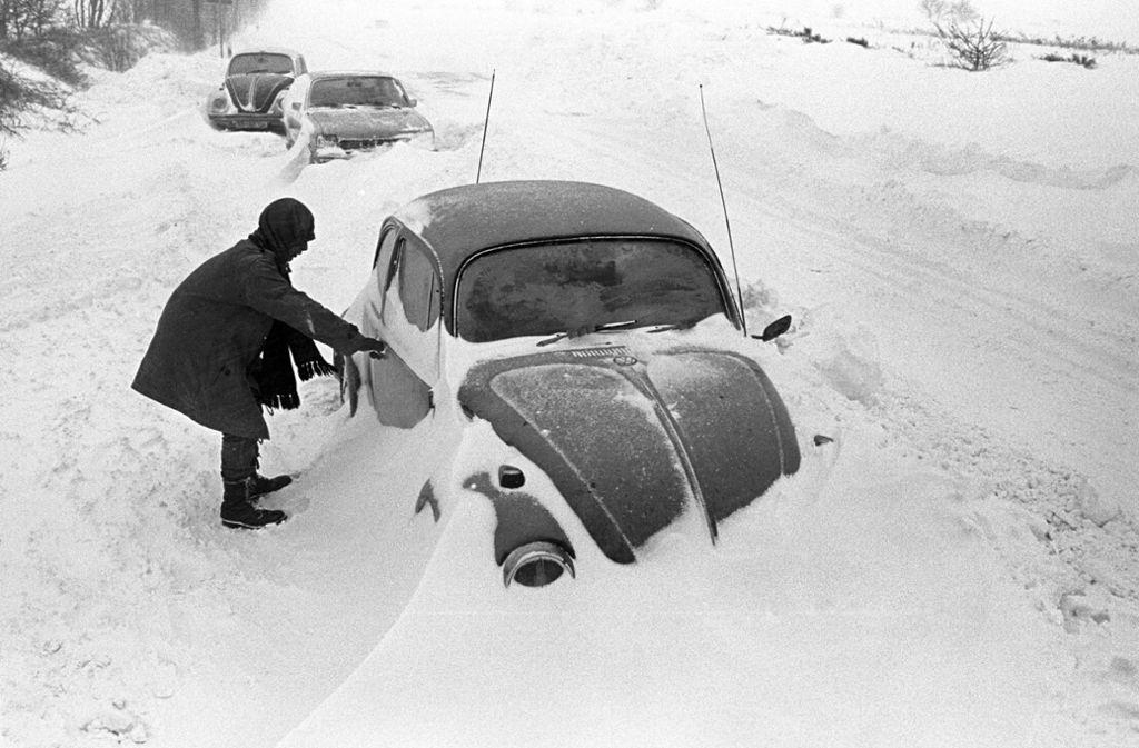 Ein Autofahrer steht neben seinem am Straßenrand im Schnee stecken gebliebenen VW-Käfer, aufgenommen bei Cuxhaven am 31. Dezember 1978. Der Temperatursturz vom 29. Dezember 1978 führte in Norddeutschland, dem Norden der DDR, Dänemark und Südschweden zu einem Schneechaos. Foto: dpa