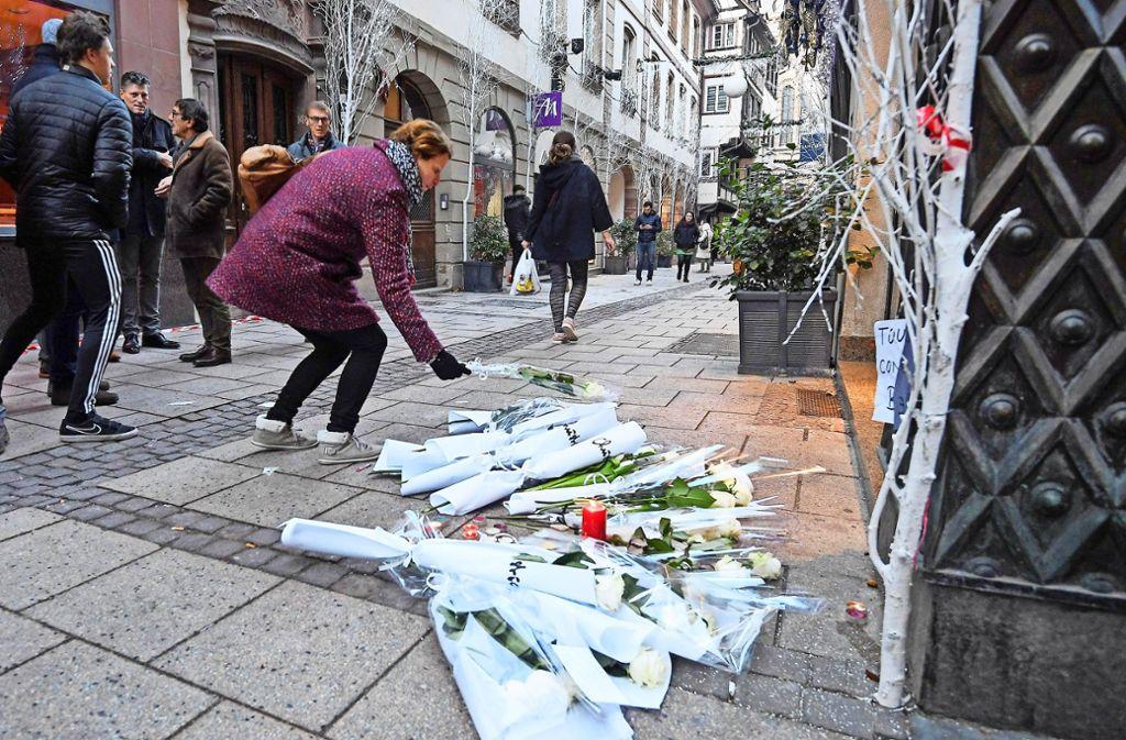 Eine Frau legt an einem Tatort in Straßburg Blumen nieder. Direkt nach dem Terror in Straßburg riegelte die Polizei  die Grenze bei Kehl ab... Präsident Foto: AFP