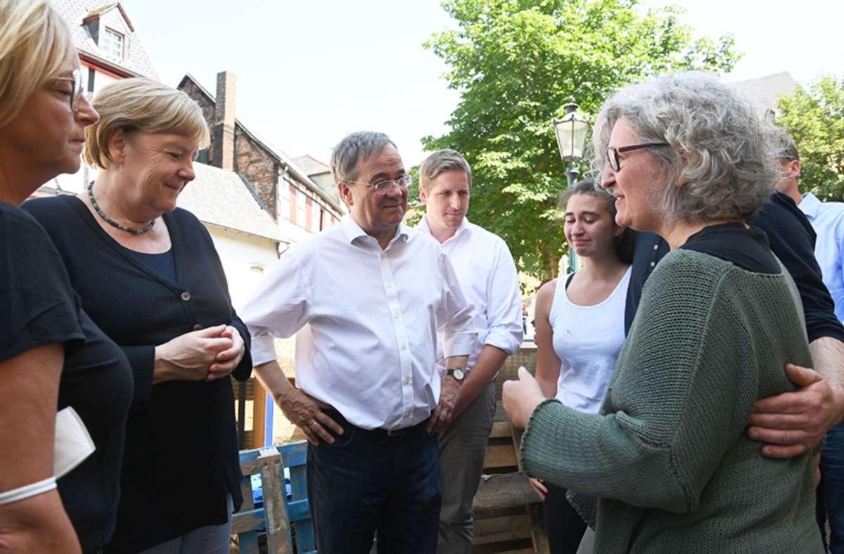 Kanzlerin Angela Merkel und NRW-Ministerpräsident Armin Laschet im Gespräch mit Betroffenen der Flutkatastrophe in Bad Münstereifel. Foto: dpa/Christof Stache