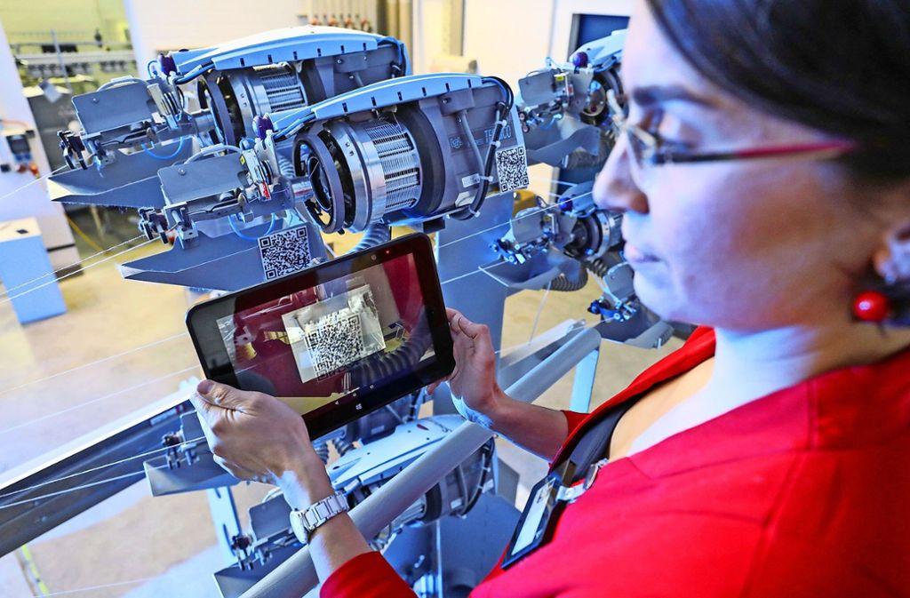 Eine Mitarbeiterin scannt mit einem Tablet QR-Codes an den Schussspulen einer Webmaschine. Auch in modernen Fabriken spielt der freie Datenfluss eine wichtige Rolle. Foto: dpa