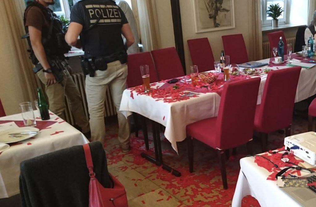Polizisten stehen in einem Veranstaltungsraum, in dem der Boden und die Tische mit Konfetti übersät sind. Bei einer AfD Veranstaltung störten Vermummte die Versammlung mit Konfetti-Kanonenschüssen. Foto: AfD Heilbronn/dpa