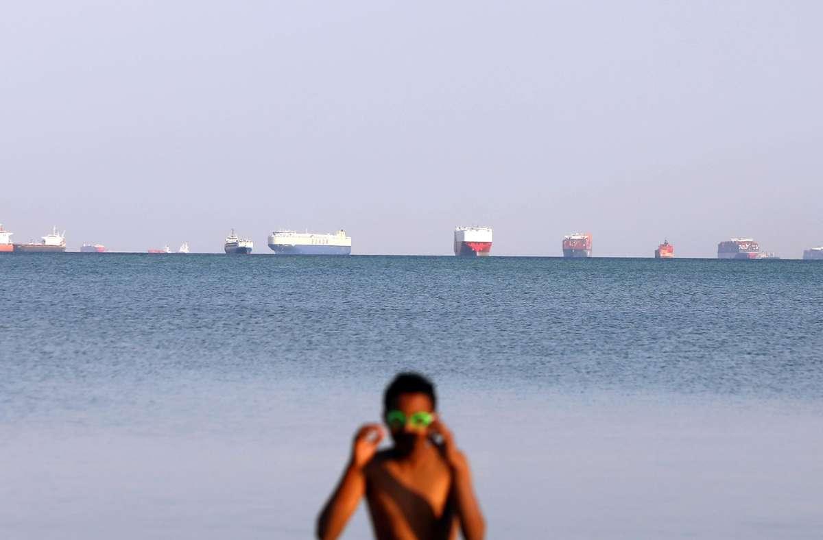 Eine Frau  im Badeanzug am Suez-Kanal – im Hintergrund ist der Stau sichtbar, den das feststeckende Containerschiff ausgelöst hat. Foto: dpa/Ahmed Gomaa