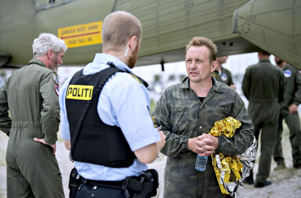 Peter Madsen (rechts) am 11. August im Gespräch mit einem Polizisten nach seiner Rettung aus dem gesunkenen U-Boot. Foto: dpa