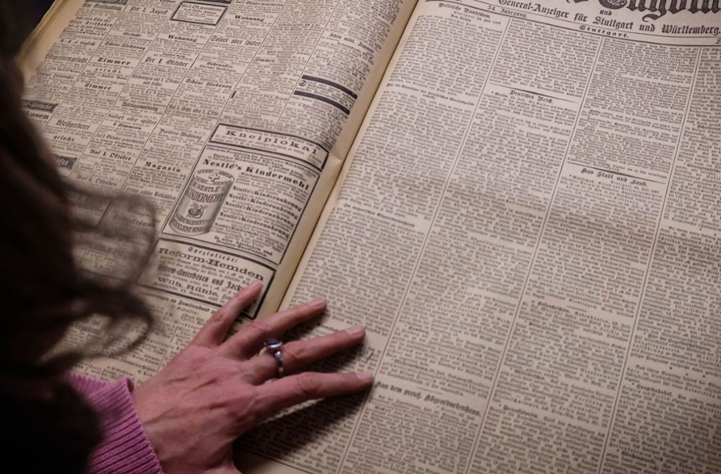 Martina Lüll, die Vizechefin der Württembergischen Landesbibliothek, begutachtet ein Original des Stuttgarter Neuen Tagblatts vom 1. Juli 1897. Foto: Lichtgut/Achim Zweygarth